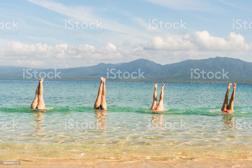 Four women handstand in turquoise sea stock photo