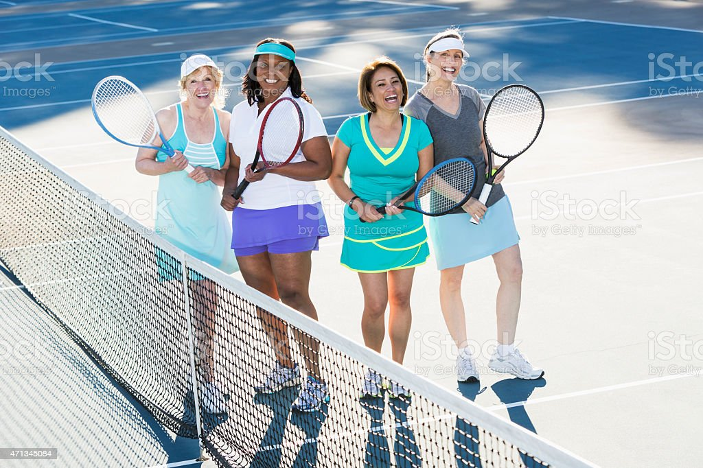 Four women playing tennis stock photo