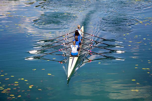 4 つの女性は、静かな湖に漕ぎ - パドルスポーツ ストックフォトと画像