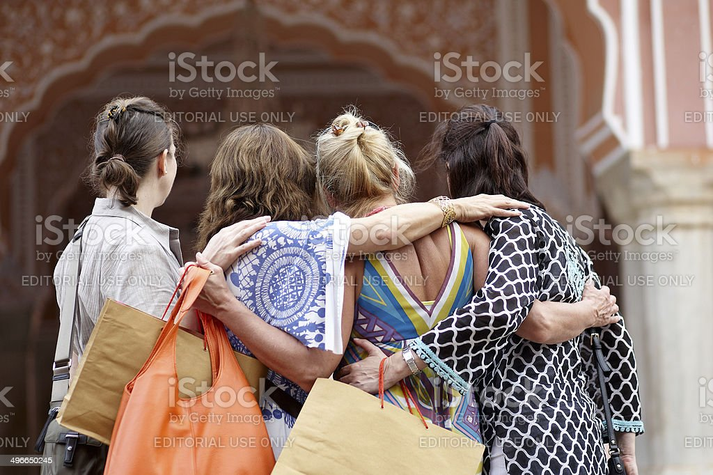 Four women tourists posing for photo rear view royalty-free stock photo