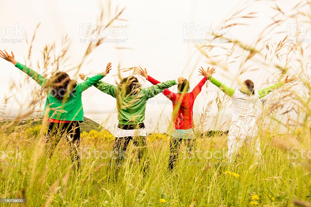 Four women with outstretched arms enjoying nature royalty-free stock photo