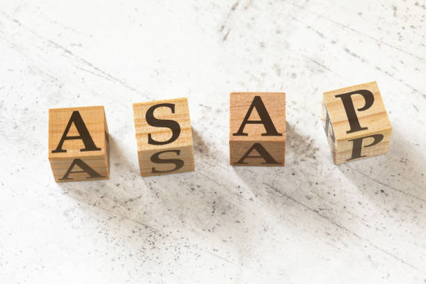 Four wooden cubes with letters ASAP (meaning As soon as possible) on white working board. Four wooden cubes with letters ASAP (meaning As soon as possible) on white working board. ASAP stock pictures, royalty-free photos & images