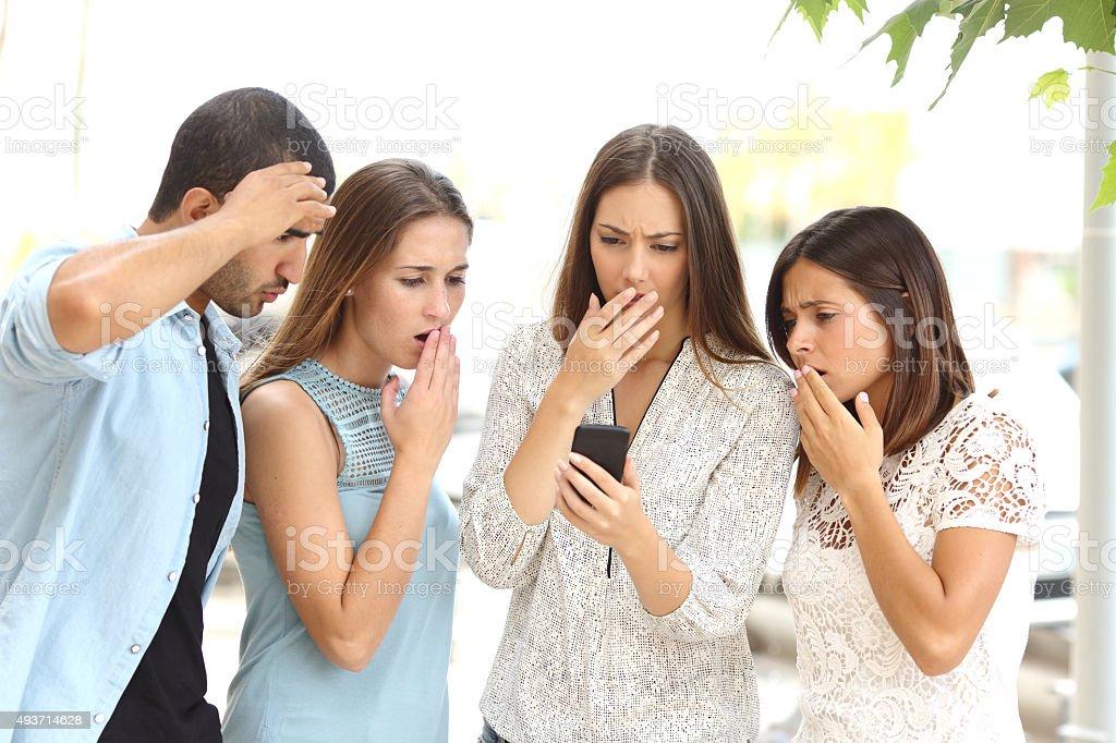 Cuatro preocupado amigos mirando teléfono inteligente - foto de stock