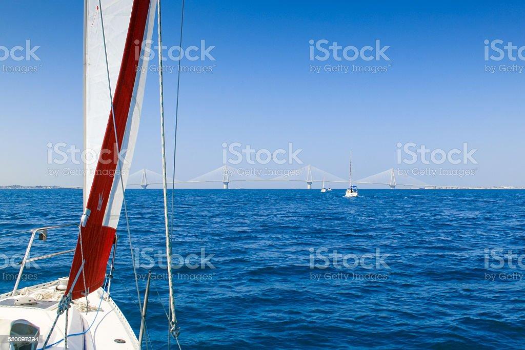 Four yachts motoring the Corinthian Gulf, towards Antirrio Suspension Bridge. stock photo