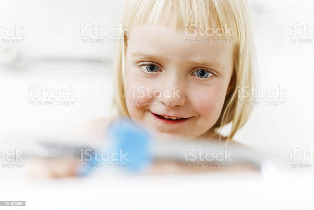 Four year old blonde girl concentrating on bath toys stock photo