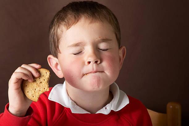vier jahre alter junge isst schokolade sandwich - schokoladenplätzchen stock-fotos und bilder