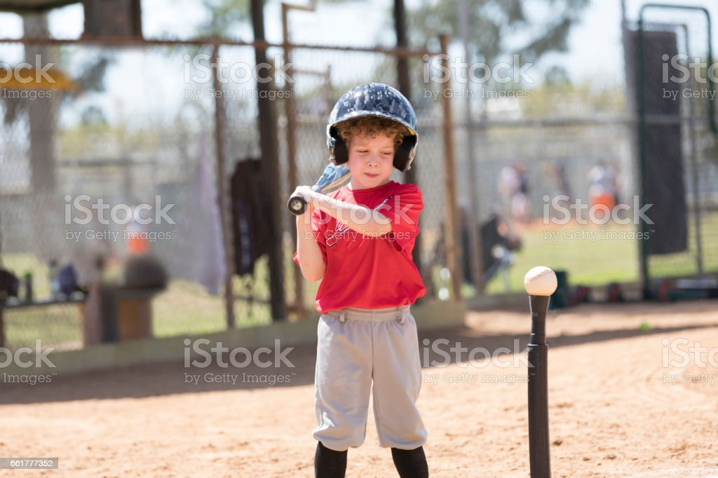 Four Year Old Boy Gets Ready to Hit a Baseball During a T-Ball Baseball Game stock photo