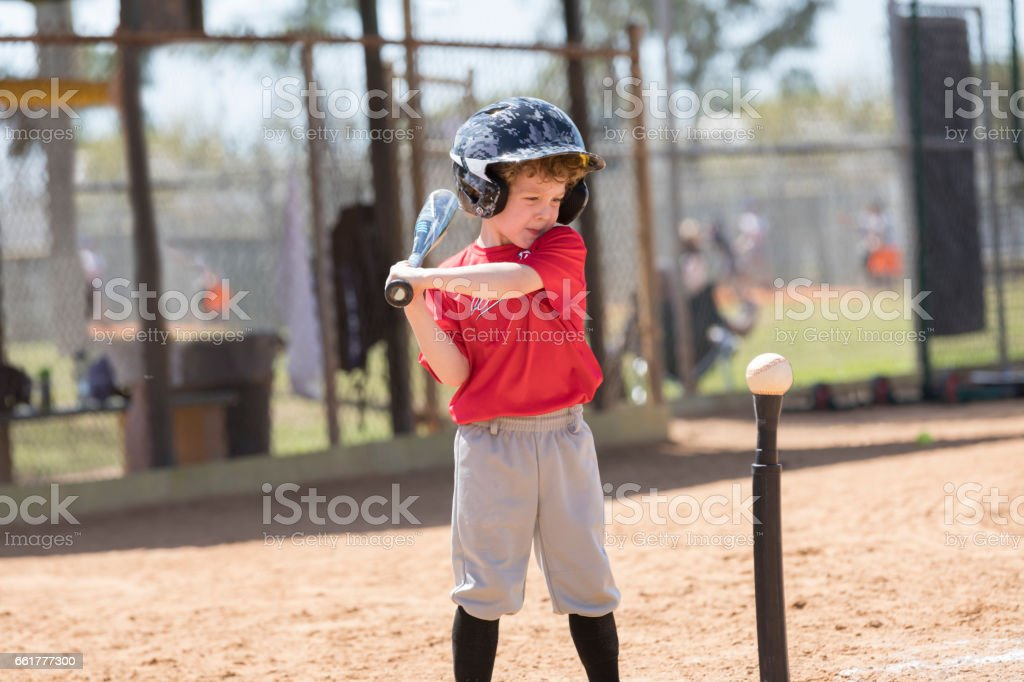 Four Year Old Boy Gets Ready to Swing a Baseball Bat at a T-Ball Game stock photo