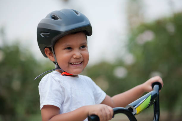 A four year old boy smiles, while wearing his bicycle helmet for safety and holding on to the bike's handle bars. stock photo