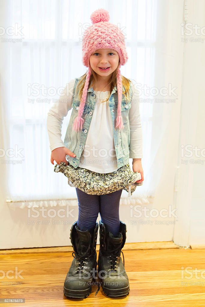 Four year old caucasian girl wearing her father's boots stock photo