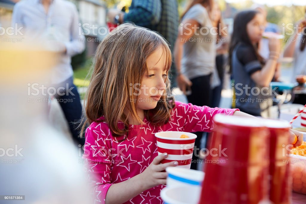 Four year old girl helping herself to food at a block party stock photo
