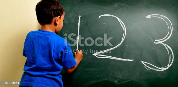 istock four year old Indian boy writing 123 on chalk board 149119581