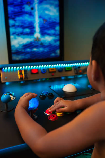 Four year old kid playing retro games on a home arcade with lighted joystick and buttons on a vertical monitor. stock photo