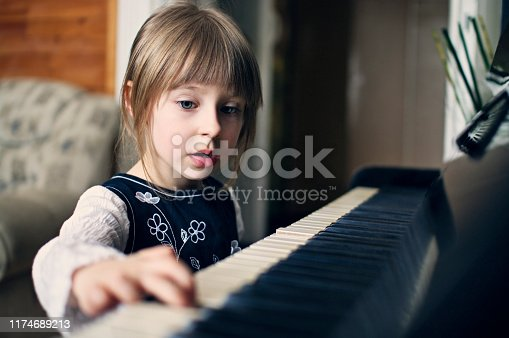 Cute little girl aged 4 is playing the old piano.