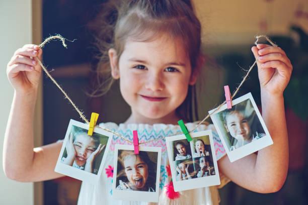 Vier Jahre alten Mädchen halten Zeichenfolge der Sofortbilder – Foto