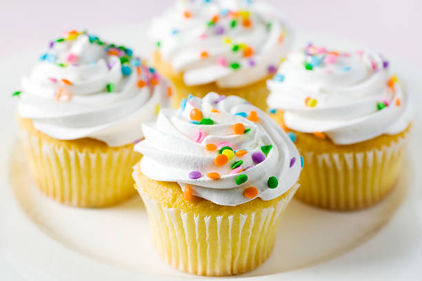 Four yellow cake and white frosted cupcakes with confetti stock photo