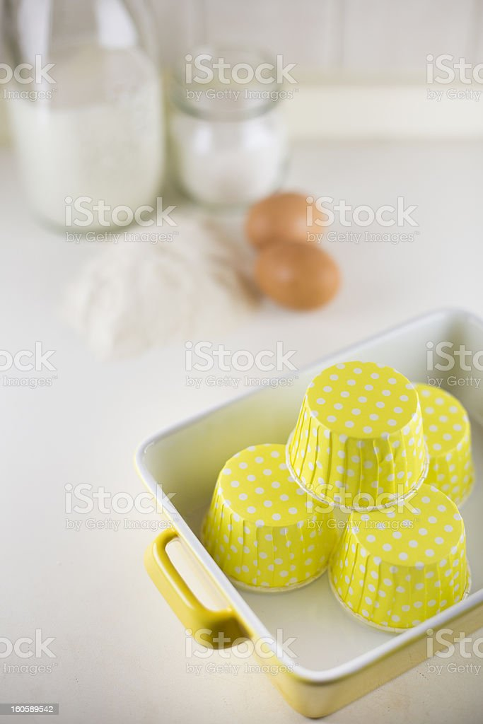 Four yellow cupcake liners and ingredients for the recipe stock photo