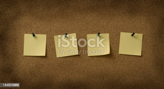 istock four yellow notes pinned to grunge cork background 144324688
