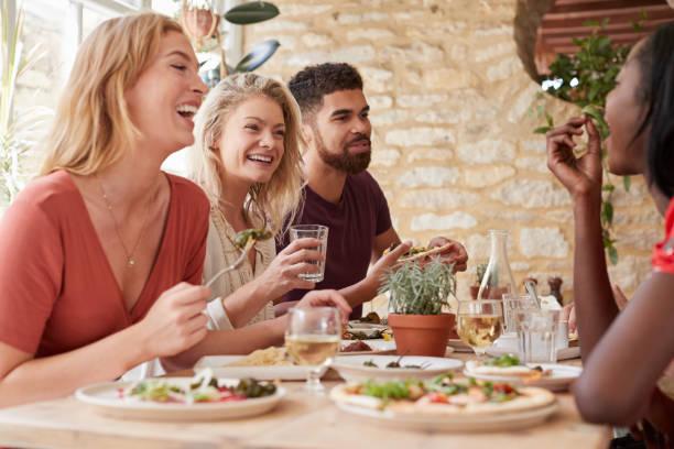 quatro jovens amigos adultos comendo em um restaurante, close-up - dia do cliente - fotografias e filmes do acervo