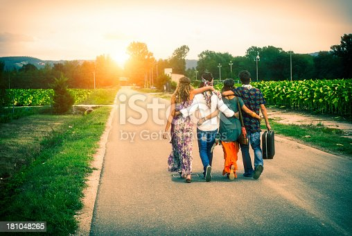 Four young adult hippie friends walking on countryside against sunset.