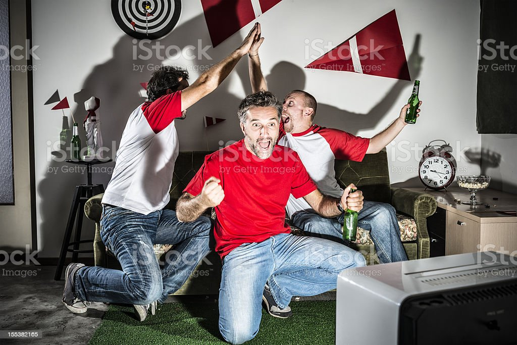 Four young adult men friends watching football: High-five goal! stock photo