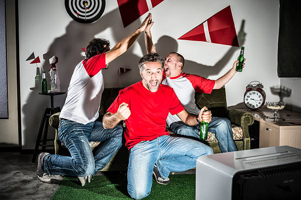 Four young adult men friends watching football: High-five goal! Four young adult men friends watching football: High-five goal! man cave couch stock pictures, royalty-free photos & images