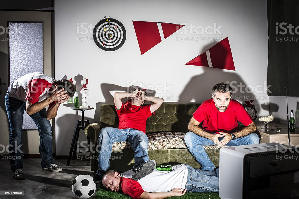 Four young adult men friends watching football on television: Defeat stock photo