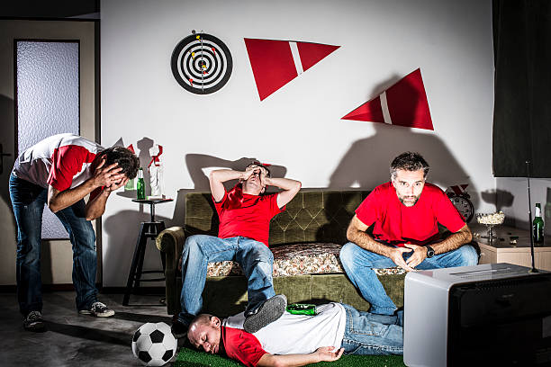Four young adult men friends watching football on television: Defeat Four young adult men friends watching football on television: Defeat man cave couch stock pictures, royalty-free photos & images