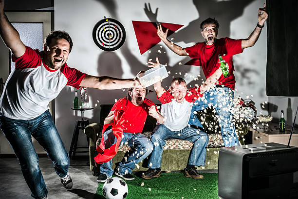 Four young adult men friends watching football on television: Goal! Four young adult men friends watching football on television: Goal! man cave couch stock pictures, royalty-free photos & images