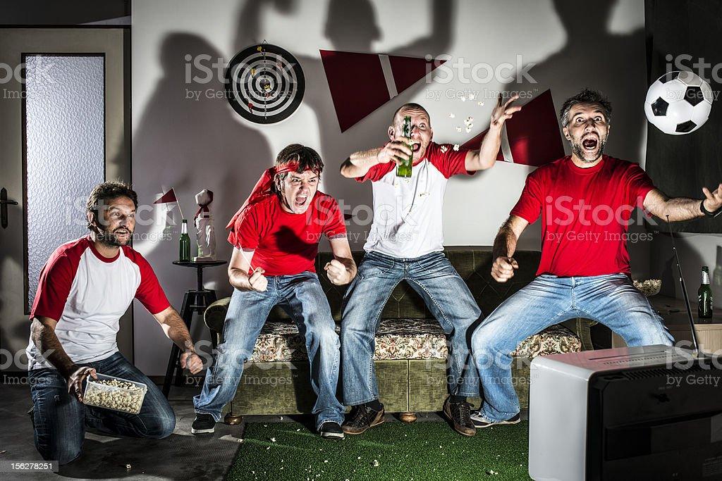 Cuatro adultos, hombres jóvenes amigos viendo el fútbol en televisión: Objetivo. - foto de stock