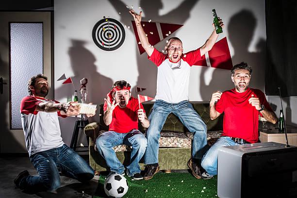 vier junge erwachsene männer freunde beobachten fußballspiel auf fernseher: tor! - fußball themenzimmer stock-fotos und bilder