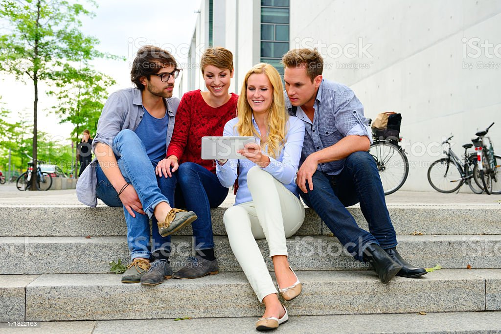 Four young adults in stairs around tablet computer stock photo