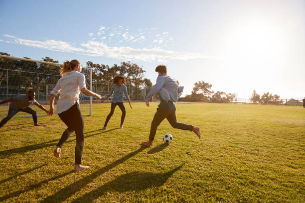 Four young adults playing football in a park at sunset stock photo