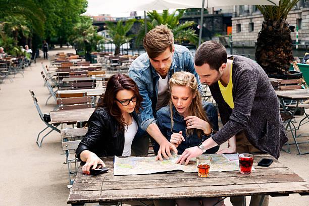 Vier junge Erwachsene mit Karte im Café – Foto