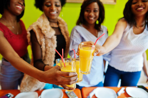 Four young african girls in bright colored restaurant stock photo