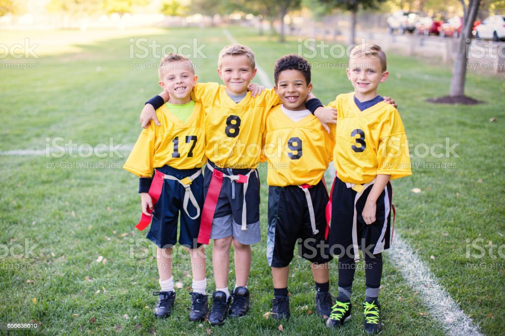Four Young Boys and Teammates Play Flag Football Lizenzfreies stock-foto