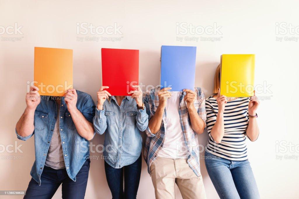 Vier jonge mensen uit het bedrijfsleven staande tegen de witte muur en mappen voor hun gezichten te houden. - Royalty-free Alleen volwassenen Stockfoto