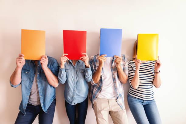vier jonge mensen uit het bedrijfsleven staande tegen de witte muur en mappen voor hun gezichten te houden. - netherlands map stockfoto's en -beelden
