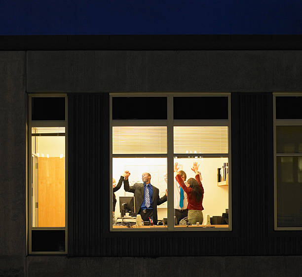 Four young businesspeople celebrating in office, view through window stock photo