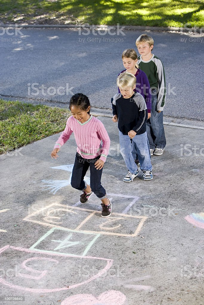 Four young children playing hopscotch stock photo