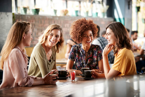 Four Young Female Friends Meeting Sit At Table In Coffee Shop And Talk stock photo