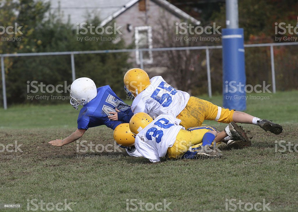 Four young football players tumble to the ground in a tackle stock photo