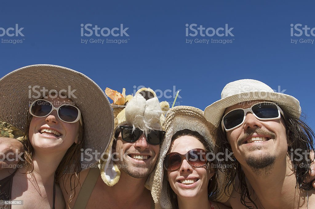 four young holiday makers smiling with sunglasses foto stock royalty-free