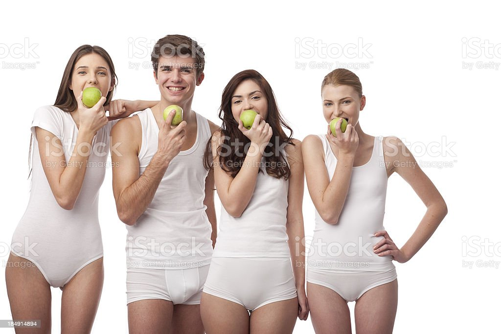 four young people eating green apples together stock photo