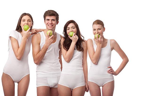 vier junge menschen zusammen essen grünen äpfeln - innocent saft stock-fotos und bilder