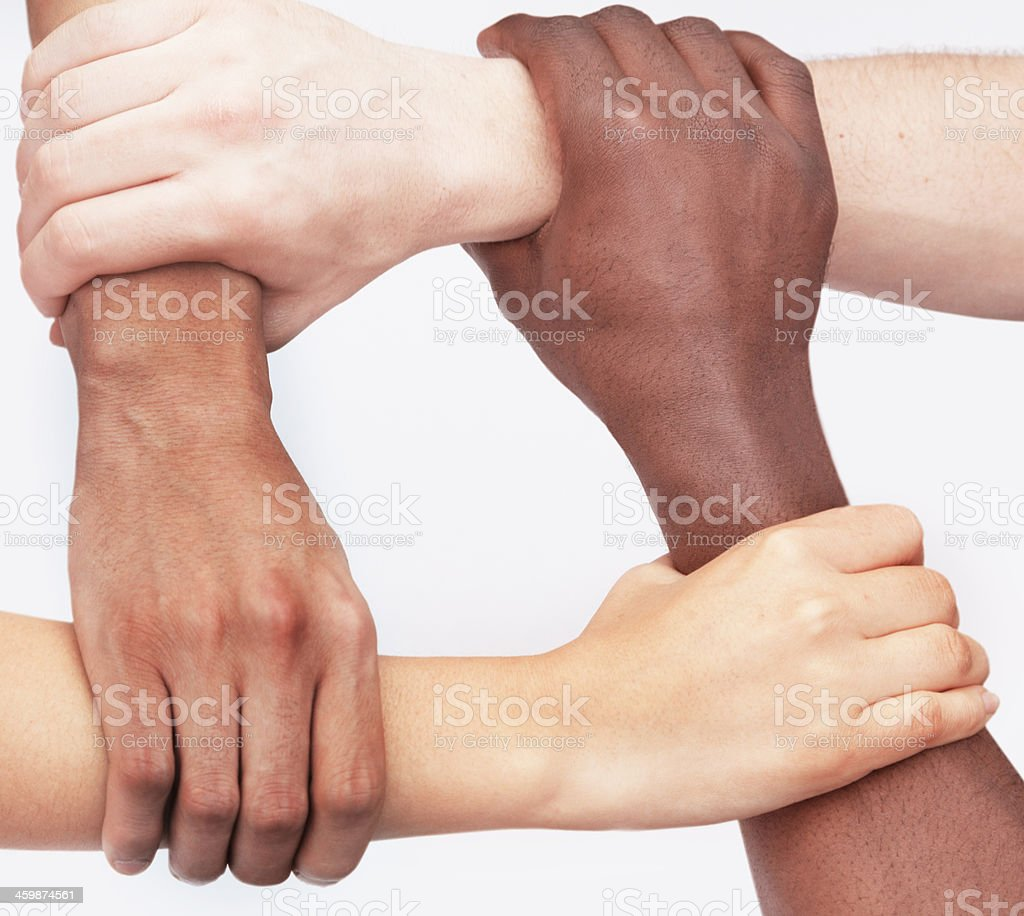 Four young people holding each others wrists in a circle, stock photo