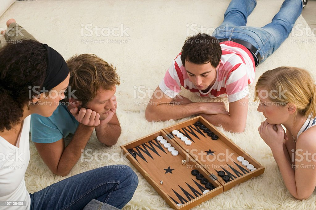 Four young people on floor playing Backgammon stock photo
