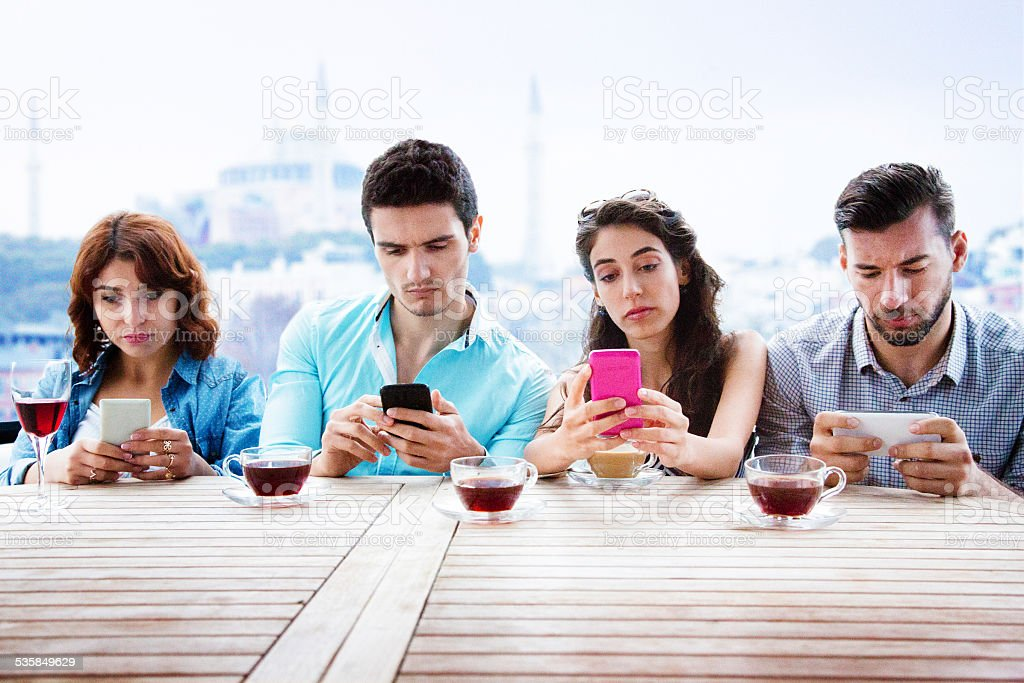 Four young people on their phones with unhappy expressions stock photo