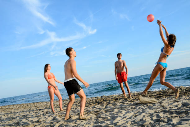 four young people playing beach volley together sea summer vacation stock photo