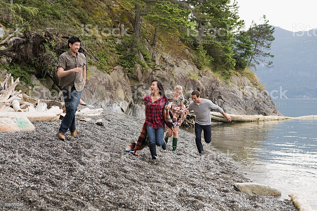 Four young people running by lake royalty-free stock photo
